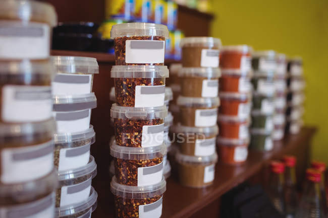 Close-up of various spices jars arranged on shelf in shop — Stock Photo