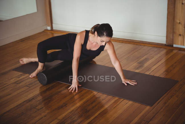 Healthy woman exercising with foam roll in fitness studio — Stock Photo
