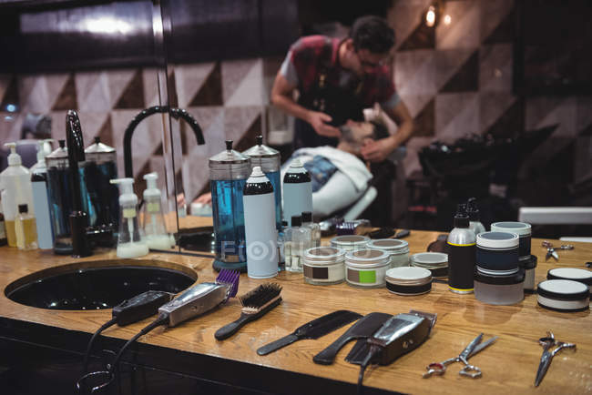 Various beauty products and barber tools on dressing table with people in background in barber shop — Stock Photo