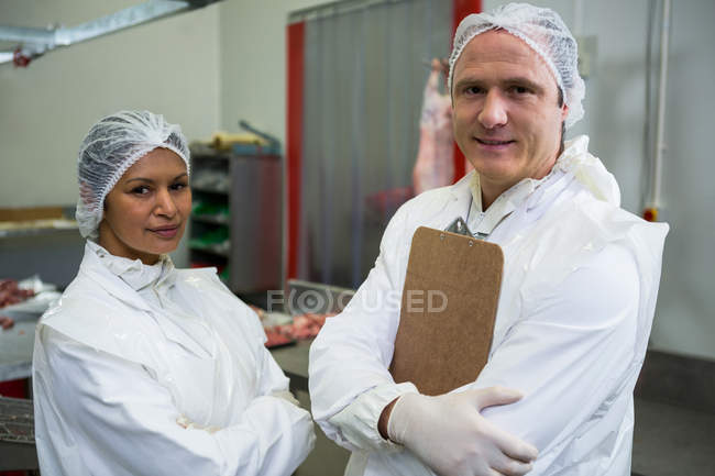 Portrait of butchers standing with arms crossed in meat factory — Stock Photo