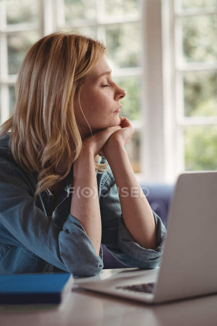 Beautiful woman relaxing at table while using laptop in living room at home — Stockfoto