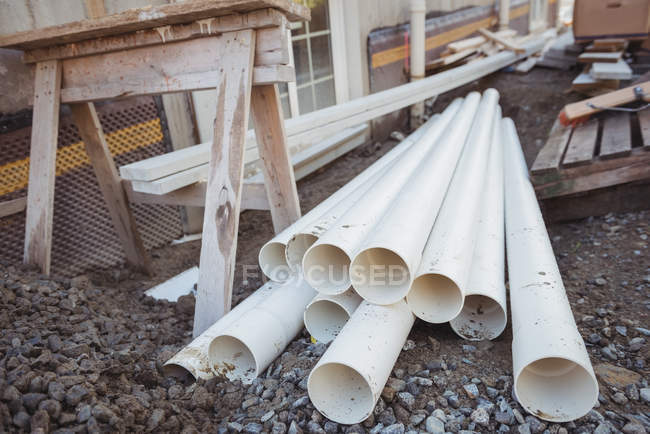 Plastic pipes and wooden planks at construction site — Stock Photo
