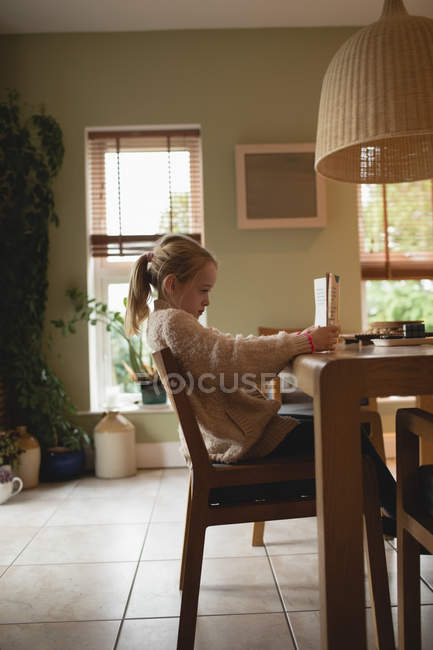 Side view of girl sitting at table and reading book at home — Stock Photo