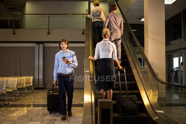 Female staff and passengers on escalator in airport — Stock Photo