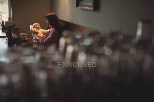 Glückliche Mutter spielt mit Baby im Café — Stockfoto