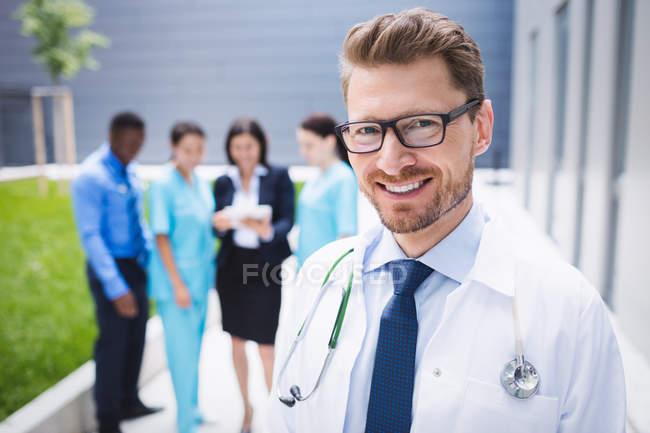 Retrato de sonriente médico permanente en los locales del hospital - foto de stock