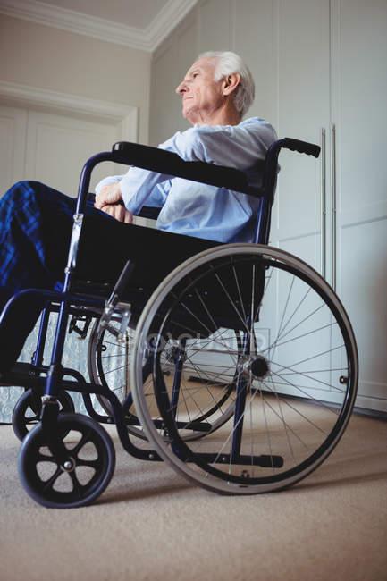 Nachdenklicher senior Mann sitzt im Rollstuhl zu Hause — Stockfoto
