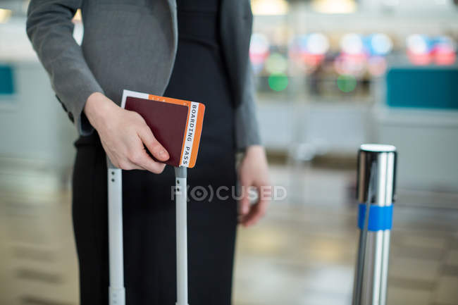 Sección media de la mujer de negocios de pie con tarjeta de embarque, pasaporte y equipaje en la terminal del aeropuerto - foto de stock