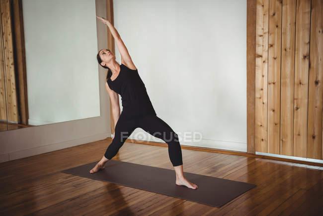 Woman performing yoga in fitness studio — Stock Photo