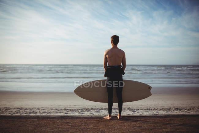 Rückansicht eines Surfers mit Surfbrett am Strand — Stockfoto