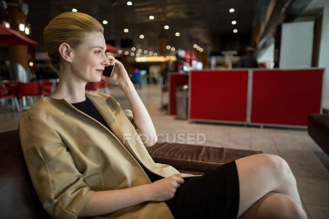 Деловая женщина разговаривает по мобильному телефону в зоне ожидания в терминале аэропорта — стоковое фото