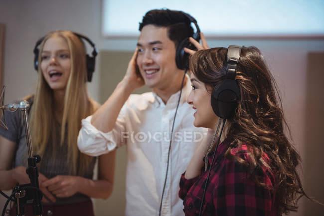 Singers with headphones performing in recording studio — Stock Photo