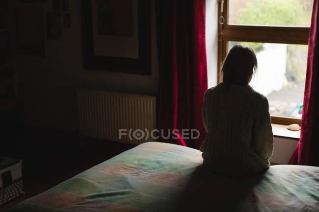 Frau sitzt auf Bett im Schlafzimmer — Stockfoto
