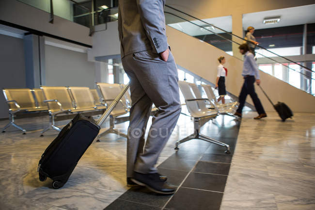 Passengers walking with luggage in waiting area at airport — Stock Photo