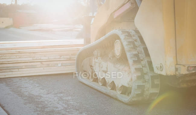 Bulldozer carrying heap of wooden planks at construction site — Stock Photo