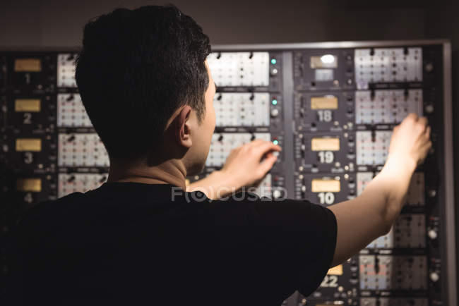 Rear view of audio engineer using track recorder in recording studio — Stock Photo