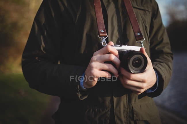Mid-section of man holding camera outdoors — Stock Photo