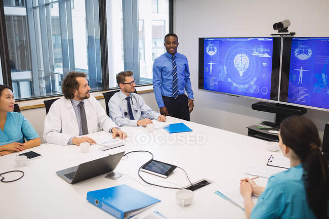 Doctor giving presentation to team of interim doctors at conference room — Stock Photo