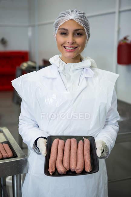 Retrato de açougueiro fêmea segurando bandeja de salsichas na fábrica de carne — Fotografia de Stock