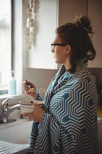 Женщина, стоя на кухне дома едят зерновые — стоковое фото
