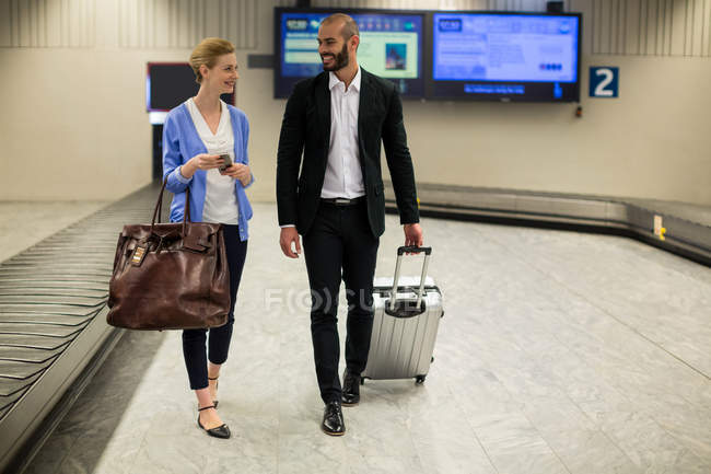 Smiling couple walking with their trolley bags in airport terminal — Stock Photo