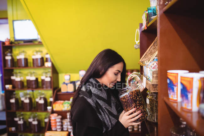 Beautiful woman smelling jar of spices in shop — Stock Photo