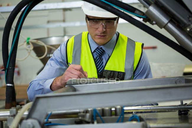 Technician examining machine at meat factory — Stock Photo