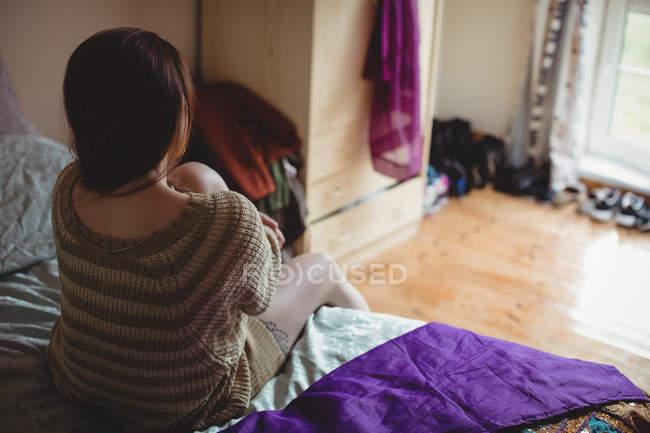 Mujer sentada en la cama en el dormitorio en casa - foto de stock