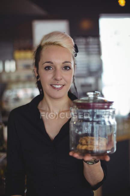 Porträt der Kellnerin halten Glas Cookies am Schalter im café — Stockfoto