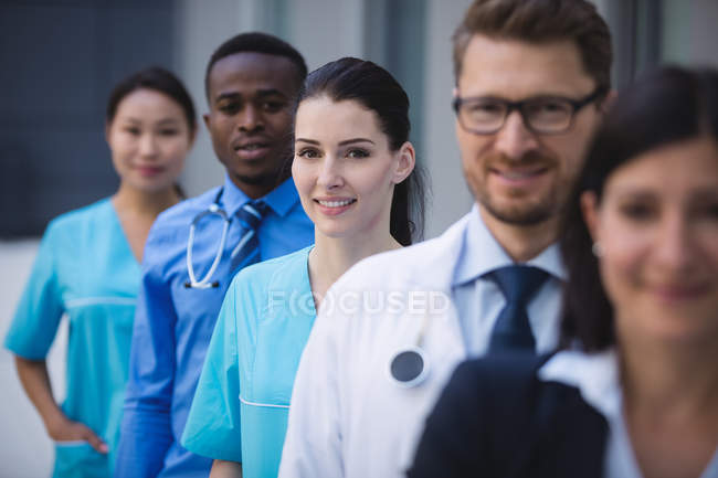 Portrait of smiling doctors standing in row at hospital premises — Stock Photo