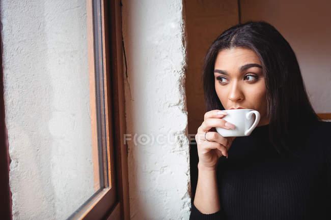Продуманий жінка за чашкою кави в кафе — стокове фото