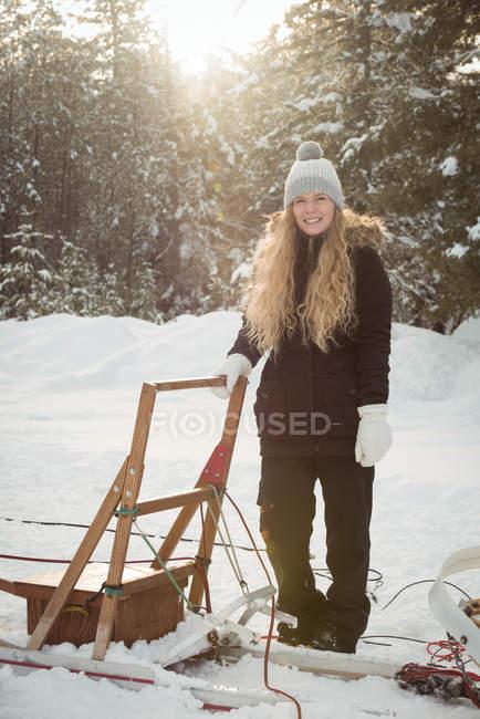 Musher femminile in piedi accanto alla slitta su un paesaggio innevato — Foto stock