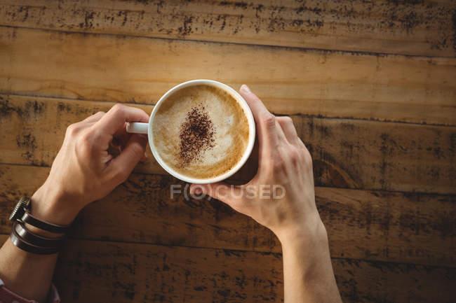 Manos de mujer sosteniendo una taza de café en la cafetería - foto de stock