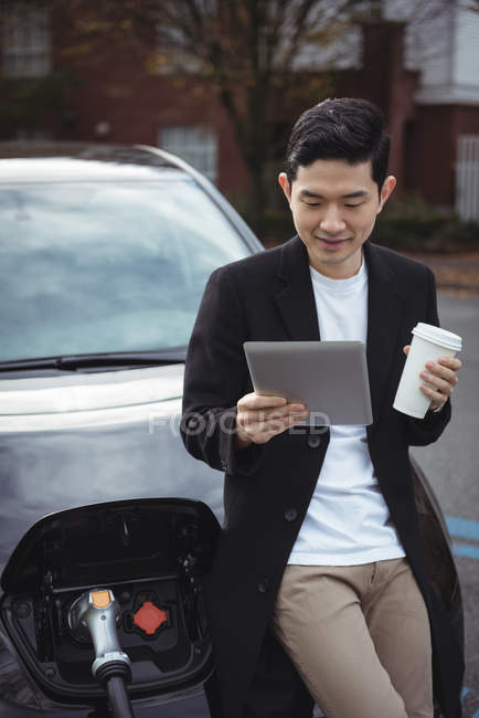 Man using digital tablet while charging car at electric vehicle charging station — Stock Photo