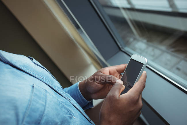 Hands of male business executive using mobile phone in office — Stock Photo