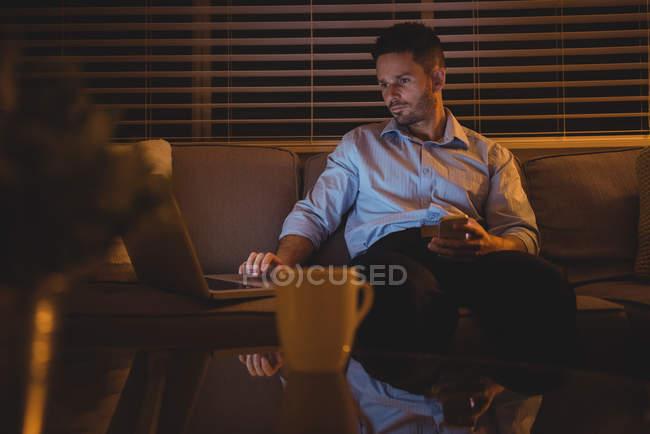 Людина, використовуючи ноутбук у вітальні на дому — стокове фото