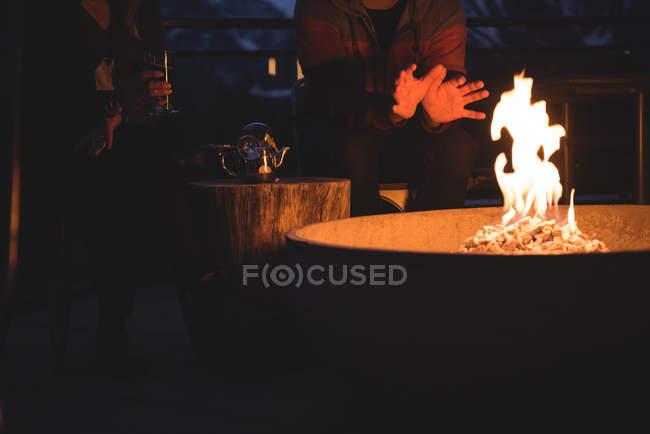 Mittelteil des Paares Feuerstelle sitzen in der Abenddämmerung — Stockfoto