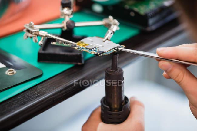 Закри людина ремонту мобільний телефон у центрі ремонту — стокове фото