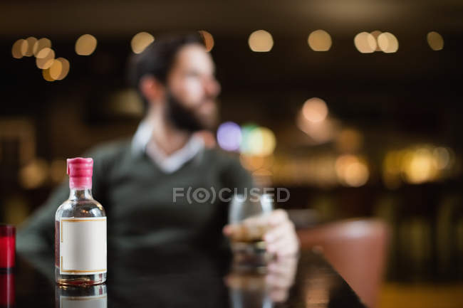 Крупный план малого ликер бутылки на стол в бар с человеком в фоновом режиме — стоковое фото