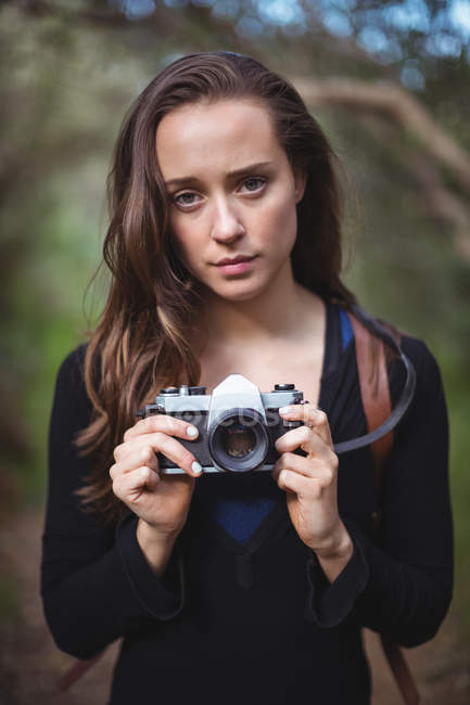 Portrait of beautiful woman standing with camera in forest — Stock Photo