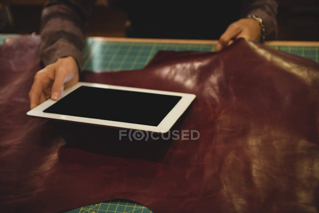 Mid-section of craftswoman using digital tablet in workshop — Stock Photo