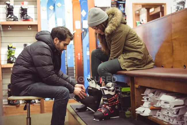 Uomo che aiuta la donna a indossare gli scarponi da sci in un negozio — Foto stock