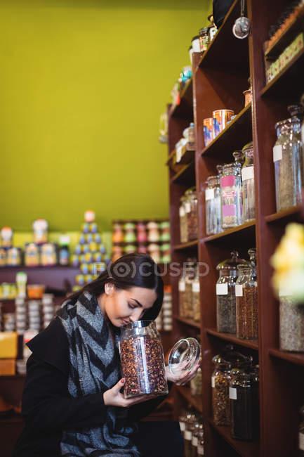 Belle femme sentant pot d'épices dans la boutique — Photo de stock