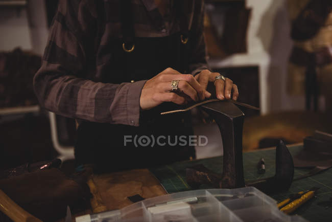 Mid-section of craftswoman hammering leather in workshop — Stock Photo