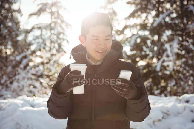 Улыбающийся мужчина в теплой одежде с помощью мобильного телефона зимой — стоковое фото