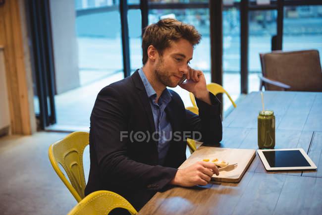 Geschäftsmann telefoniert beim Imbiss im Café — Stockfoto