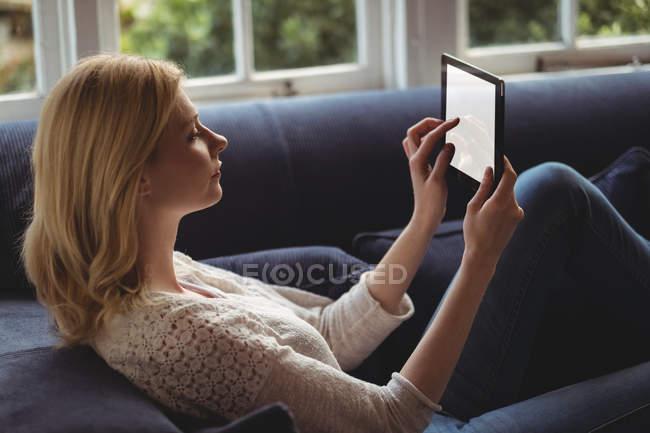 Schöne Frau sitzt auf Sofa mit digitalem Tisch im Wohnzimmer zu Hause — Stockfoto