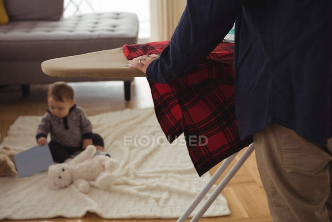 Father ironing shirt while baby playing in background at home — Stock Photo