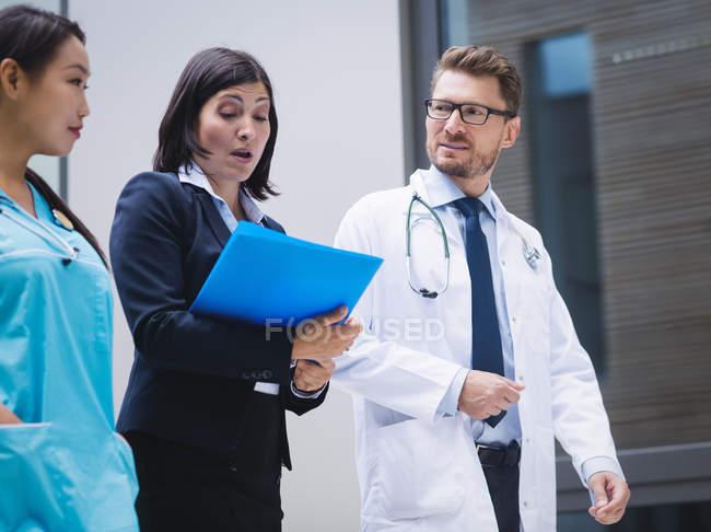 Médicos y enfermera interactuando mientras caminaba en los locales del hospital - foto de stock