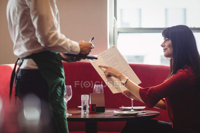 Mesero tomar la orden de mujer en un restaurante - foto de stock